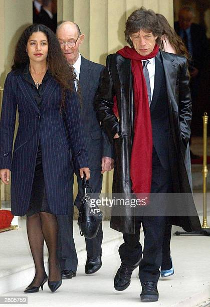 Lead singer of British group Rolling Stone Sir Mick Jagger walks with his father Joe his daughters Karis and Elizabeth after receiving his Knighthood...