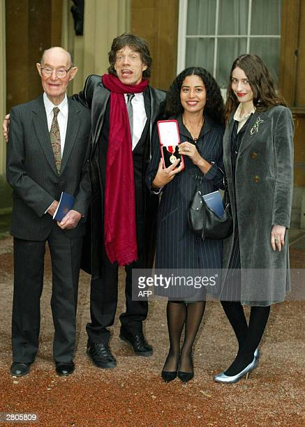 Lead singer of British group the Rolling Stone Sir Mick Jagger stands with his 92yearold father Joe and daughters Karis and Elizabeth after receiving...