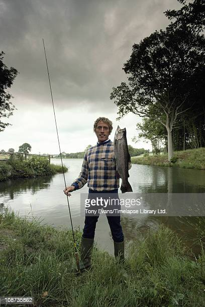 Lead singer of The Who Roger Daltrey with a fish at his trout fishery in Sussex, 1982.