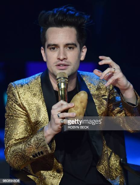 Lead singer of US band Panic At The Disco Brendon Urie holds a potato that was given to him as a gift on stage at the iHeartRadio Album Release Party...