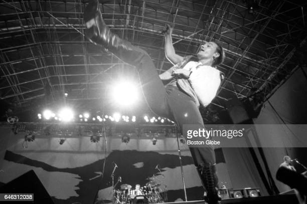Lead vocalist Bono of U2 kicks in the air as the band performs at Sullivan Stadium in Foxborough MA on Sep 22 1987 during their tour supporting The...