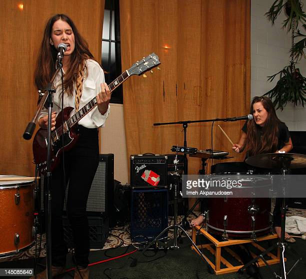 Lead vocalist/guitarist Danielle Haim and percussionist Alana Haim of HAIM perform at the Nudie Jeans event at the Palihouse on May 22 2012 in West...