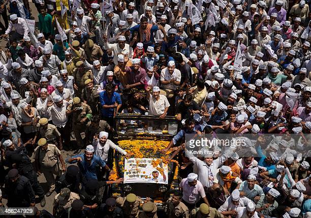 Leader and anti-corruption activist Arvin Kejriwal, centre, waves from an open jeep as he is surrounded by supporters on his way to file his...
