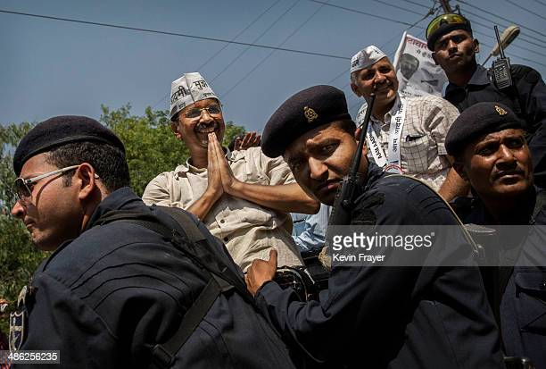Leader and anti-corruption activist Arvin Kejriwal is surrounded by police bodyguards as he greets supporters from an open jeep on his way to file...