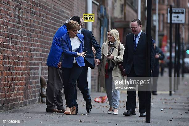 SNP leader and First Minister Nicola Sturgeon has the heel of her shoe caught by local candidate Humza Yousaf as they arrive at BAE Systems in Govan...