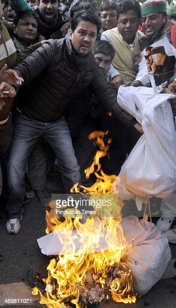 BJP leader and MP Anurag Thakur burn effigies of Virbhadra Singh and Rahul Gandhi during a protest outside the residence of Congress Vice President...