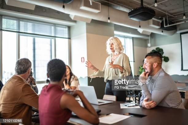 líder empresaria hablando con sus colegas en la presentación - equidad de genero fotografías e imágenes de stock