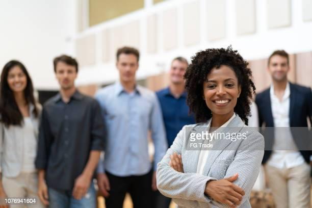 empresária de líder com a equipe de negócios confiante no plano de fundo - liderança - fotografias e filmes do acervo