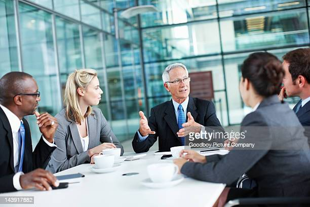 leader expressing views to associates - conference table stock pictures, royalty-free photos & images