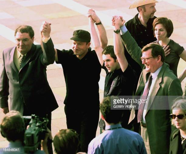 SDLP leader John Hume Bono lead singer with Irish rock group U2 Tim Wheeler with Ash and Ulster Unionist leader David Trimble link hands as they...
