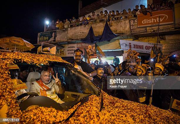 BJP leader Narendra Modi flashes the vsign to supporters as he is surrounded by bodyguards while driving through the streets on May 8 2014 in...