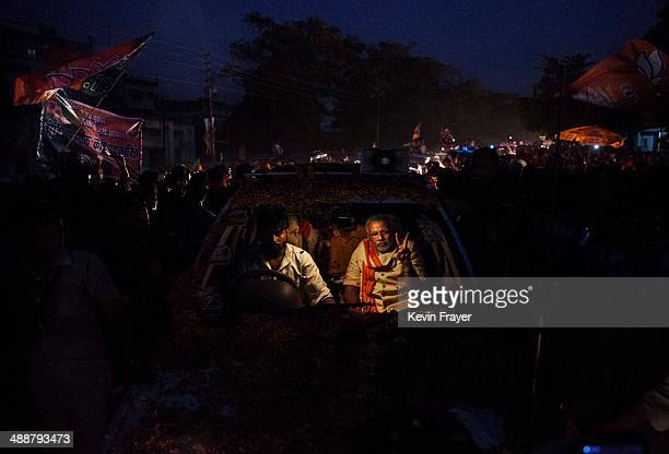 BJP leader Narendra Modi flashes the vsign while driving through the streets on May 8 2014 in Varanasi India Thousands of supporters lined the the...