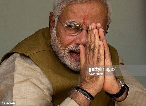 Leader Narendra Modi gestures to supporters as he sits with his mother Heeraben Modi, not seen, on her front porch after seeking her blessing on May...