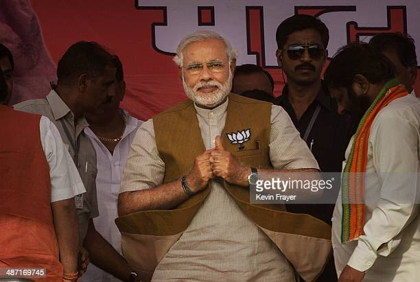 BJP leader Narendra Modi holds his waistcoat before speaking to the crowd at a rally on April 27 2014 in Sidhuali near Lucknow India India is in the...
