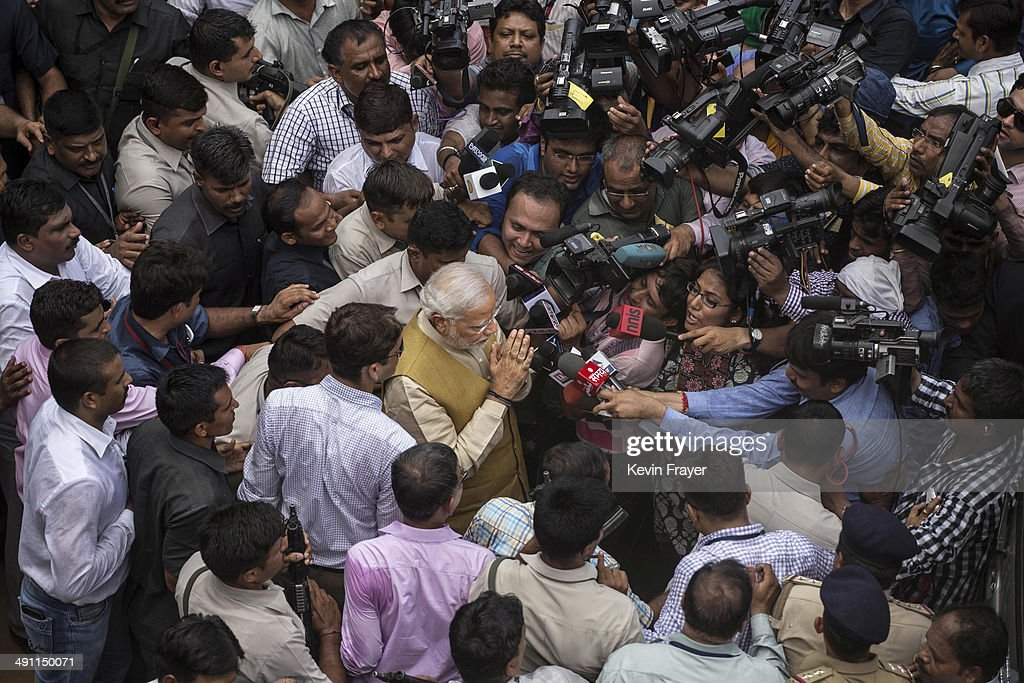 BJP leader Narendra Modi is seen as he is surrounded by supporters, security and media after visiting his mother on May 16, 2014 in Ahmedabad, India. Early indications from the Indian election results show Mr Modi's Bharatiya Janata Party was ahead in 277 of India's 543 constituencies where over 550 million votes were made, making it the largest election in history.