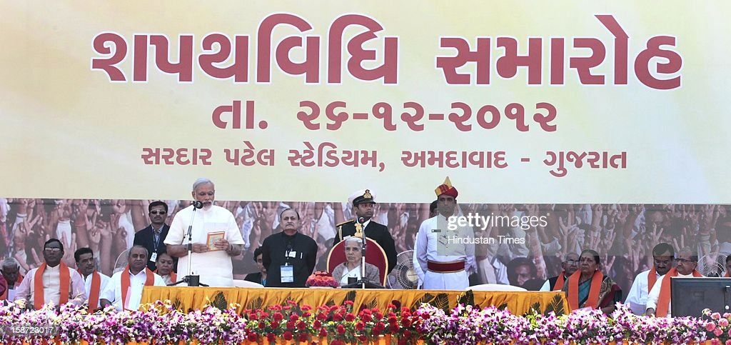 BJP Leader Narendra Modi taking oath as Gujarat's Chief Minister as Gujarat governor Kamla Beniwal (R) looks on at a grand function at Sardar Patel Stadium on December 26, 2012 in Ahmedabad, India. Narendra Modi sworn as Chief Minister of Gujarat for fourth successive term.