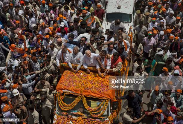 BJP leader Narendra Modi waves to supporters as he rides in an open truck on his way to filing his nomination papers on April 24 2014 in Varanasi...