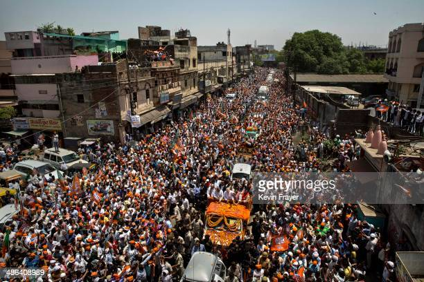 Leader Narendra Modi waves to supporters as he rides in an open truck on his way to filing his nomination papers on April 24, 2014 in Varanasi,...