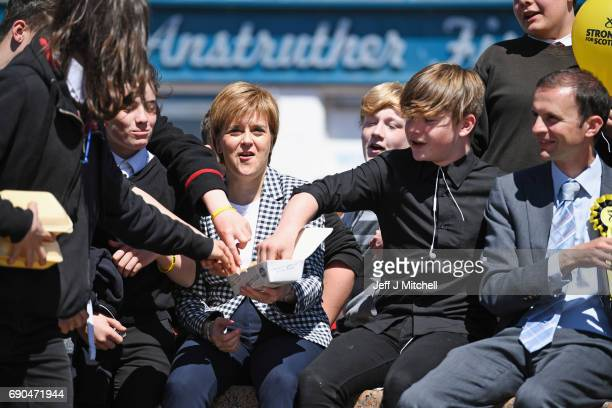 SNP leader Nicola Sturgeon shares her chips with some local school children as she campaigns with candidate Stephen Gethins on May 31 2017 in...