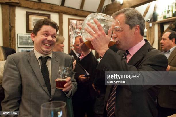 Leader Nigel Farage drinks beer from a large glass at the Bolton Arms pub after speaking at a UKIP public meeting at Old Basing Village Hall on April...