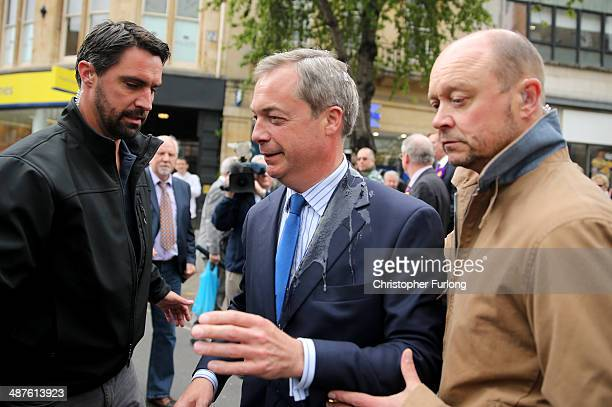 Leader Nigel Farage is lead back to his car after after being hit with an egg thrown by a man who gave his name as Fred, an unemplyed musician, on...