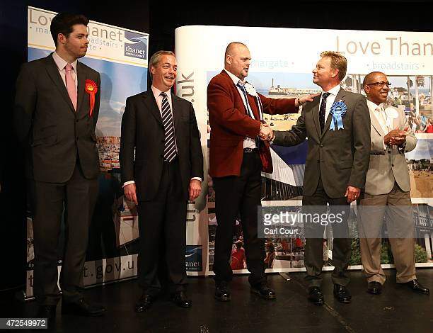 UKIP leader Nigel Farage looks on Alastair James Hay better known as comedian 'Al Murray' who portrays an English pub landlord congratulates...