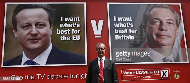 UKIP leader Nigel Farage poses for photographers as he unveils a new campaign poster Ahead Of a televised debate with the Prime Minister later today...