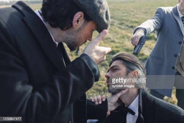 leader of bandits holding neck of detainee. - dead gangster stock pictures, royalty-free photos & images