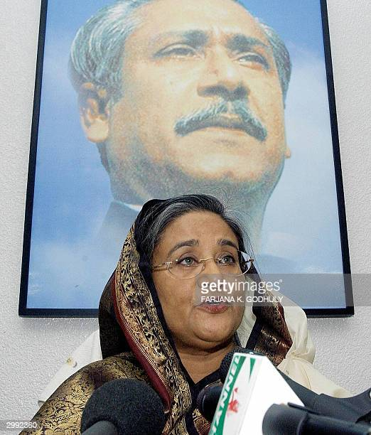 Leader of Bangladesh's main opposition party the Awami League Sheikh Hasina Wajed answers a question as she sits in front of a portrait of her Father...