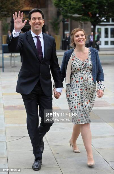 Leader of Britain's opposition Labour Party, Ed Miliband, waves as he arrives with his partner Justine Thornton, to address delegates on the third...