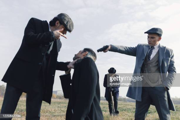 leader of criminal crew talking to detainee. - dead gangster stock pictures, royalty-free photos & images