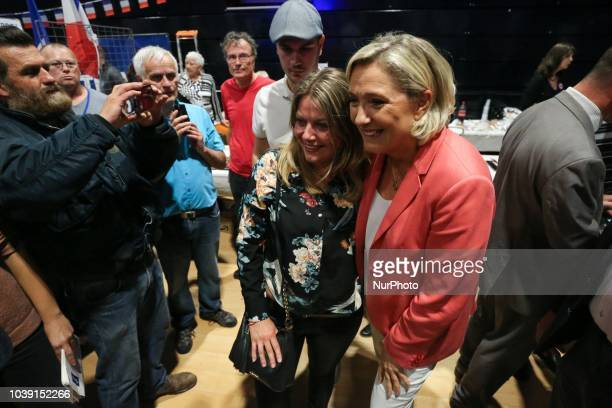 Leader of France's Rassemblement National farright political party Marine Le Pen poses for photographs with supporters during RN party's fair Fete du...
