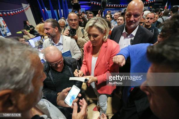Leader of France's Rassemblement National farright political party Marine Le Pen signs autographs during RN party's fair Fete du drapeau on September...