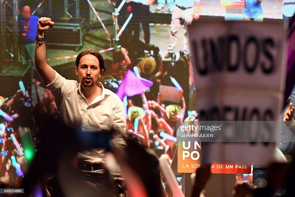 Leader of left wing party Podemos and party candidate, Pablo Iglesias raises his fist as he delivers a speech moments before the official results at Reina Sofia square during Spain's general elections in Madrid on June 26, 2016. Spain's incumbent conservatives stole the show away from a far-left coalition led by Podemos on June 26, finishing stronger in repeat elections with more seats than in December polls though still without a majority. / AFP / GERARD