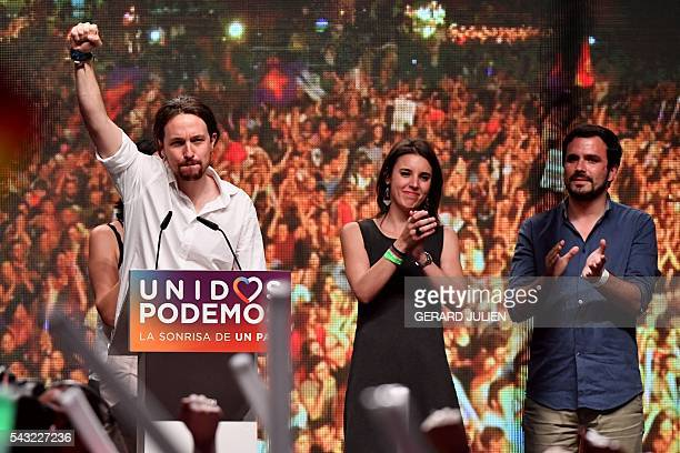 Leader of left wing party Podemos and party candidate Pablo Iglesias raises his fist past Leftwing Podemos member and Madrid candidate congress the...