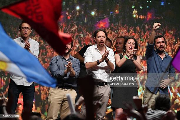 Leader of left wing party Podemos and party candidate Pablo Iglesias applauds with leftwing Podemos member and Irene Montero leftwing party IU leader...
