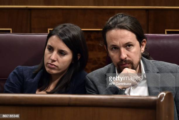 Leader of left wing party Podemos Pablo Iglesias sits beside Podemos MP Irene Montero at the Spanish Parliament in Madrid on October 11 2017 Spain...