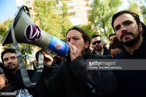 Leader of left-wing party Podemos, Pablo Iglesias uses a megaphone beside leader of Izquierda Unida party, Alberto Garzon as they take part in a...