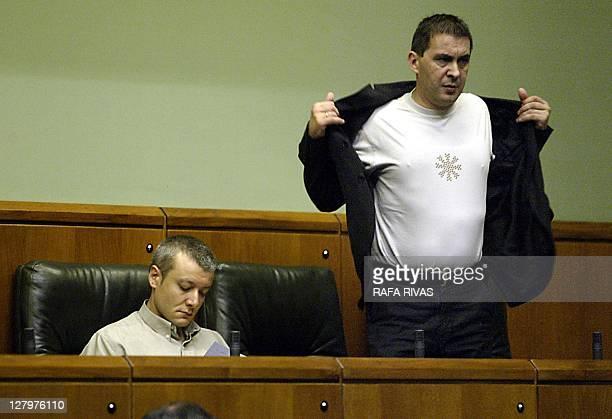 Leader of outlawed party Batasuna and deputy of Sozialista Abertzaleak Arnaldo Otegi takes off his jacket as SA deputy Antton Morcillo sits during a...