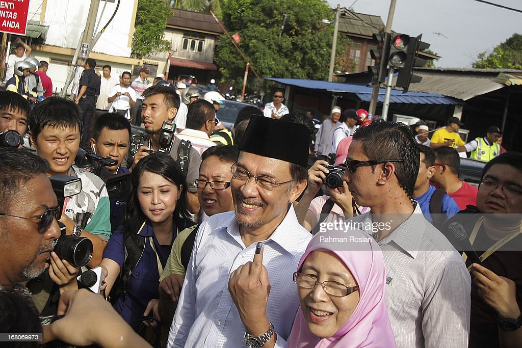 Leader of Pakatan Rakyat, Anwar Ibrahim and his wife, Wan Azizah greet their supporters after casting their votes on May 5, 2013 in Penanti, Penang, Malaysia. Millions of Malaysians cast their vote on Sunday in one of the most tightly contested Malaysian election since independence in 1957. The opposition coalition, Pakatan Rakyat (People's Alliance), led by former deputy prime minister Anwar Ibrahim is seeking to gain power on a national level against the ruling party Barisan Nasional.