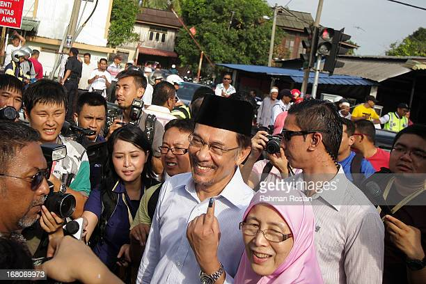Leader of Pakatan Rakyat Anwar Ibrahim and his wife Wan Azizah greet their supporters after casting their votes on May 5 2013 in Penanti Penang...