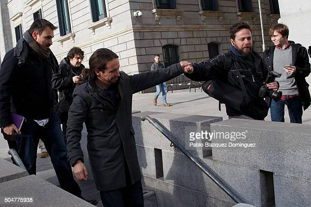 Leader of Podemos party Pablo Iglesias shake hands with a man as he leaves after the inaugural meeting of the eleventh legislature of the Congress of...