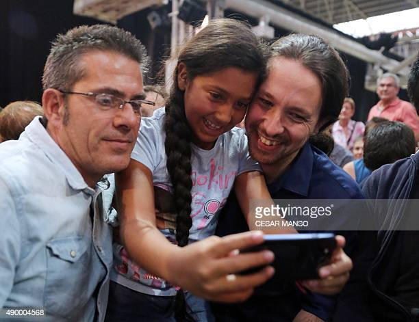 Leader of Podemos political party Pablo Iglesias poses for a 'selfie' with a father and child during the party's final campaign of political party...