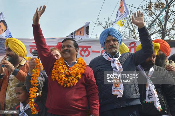 Leader of the Aam Aadmi Party and Chief minister of Delhi Arvind Kejriwal and AAP candidate for Amritsar Lok Sabha bypoll Upkar Singh Sandhu wave to...