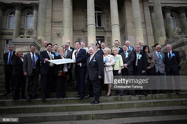 Leader of the Conservative party David Cameron poses with all the tory candidates as he receives a cheque on the steps of Bolton Town Hall on April...