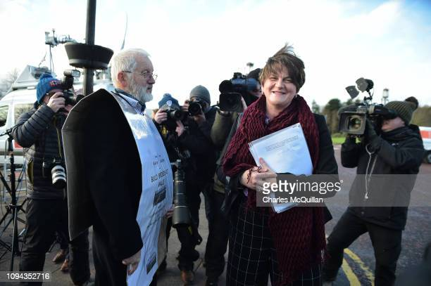 Leader of the DUP Arlene Foster is confronted by a protestor wearing a Build Bridges not Walls sandwich board as she attends a press conference...