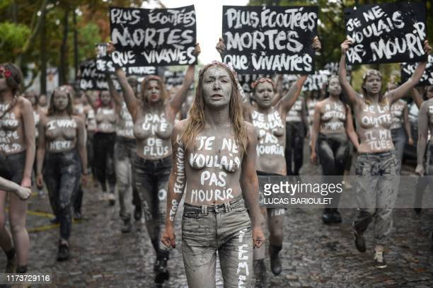 TOPSHOT Leader of the feminist activist group Femen Inna Shevchenko and Femen activists hold placards reading More heard dead than alive I didn't...