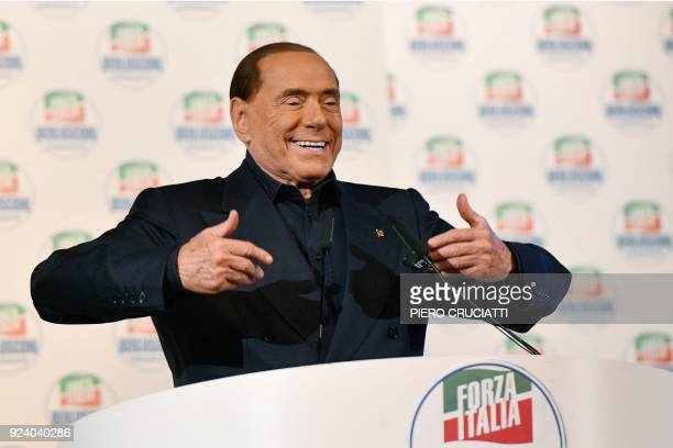 Leader of the Italian rightwing party Forza Italia Silvio Berlusconi gestures as he delivers a speech on stage during a campaign rally in Milan on...