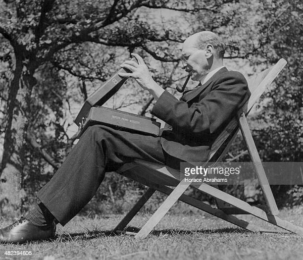 Leader of the Labour Party Clement Attlee sitting in a deck chair at his home reading government documents in his spare time England circa 19511955