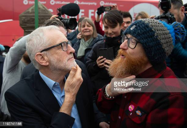 Leader of the Labour Party Jeremy Corbyn compares his beard with a supporter after arriving at the Patti Pavilion on December 7, 2019 in Swansea,...